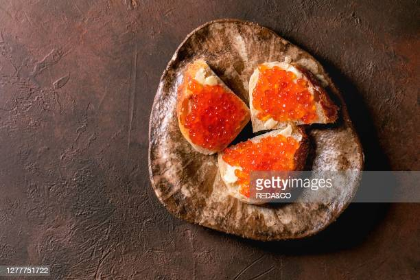Red salmon caviar on wheat bread with butter on ceramic plate over dark brown texture background. Flat lay. Space.