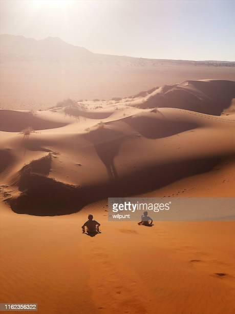 red sand dune sand boarding fun sliding down - sand dune stock pictures, royalty-free photos & images