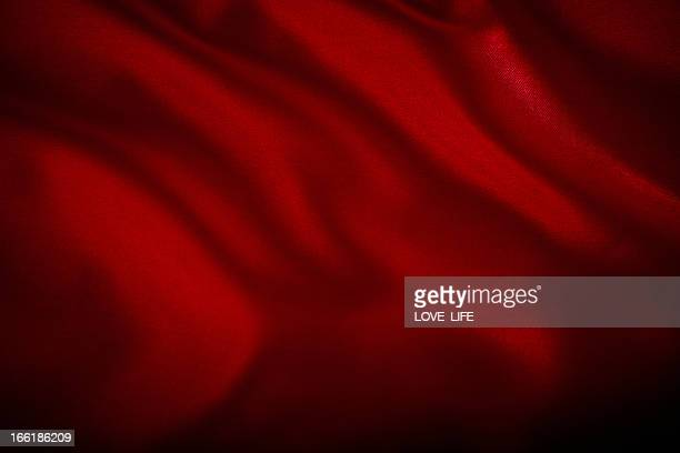 A red satin cloth background with wrinkles