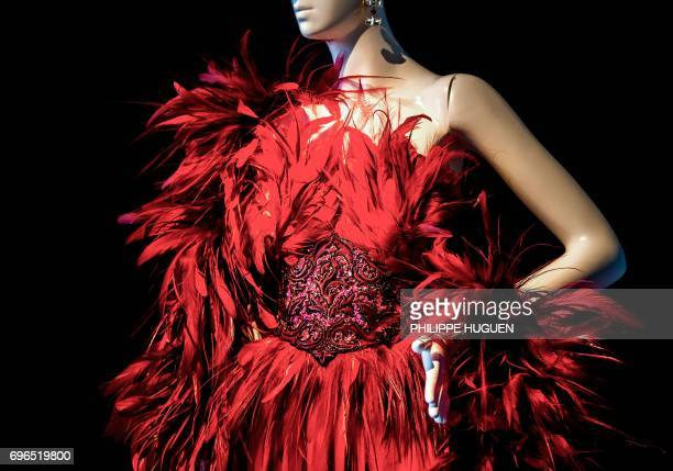A 1988 red satin evening dress with a feather ornated and sequin embroidered bodice by French fashion designer Hubert de Givenchy is pictured during...