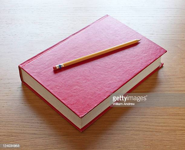 Red school book with pencil