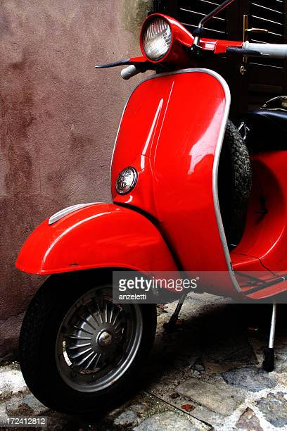 A red scooter parked beside a wall