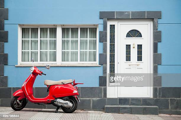 Red scooter parked in front of blue house.