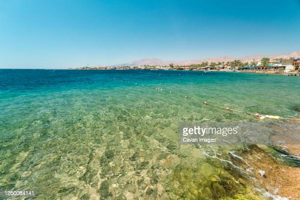 red sea dahab blue water with mountainy in the background - tourism in south sinai stock pictures, royalty-free photos & images