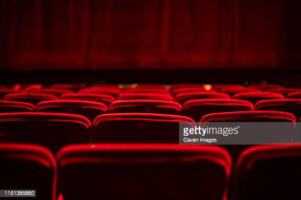 red seats and curtains of an empty theater - industrie du cinéma photos et images de collection