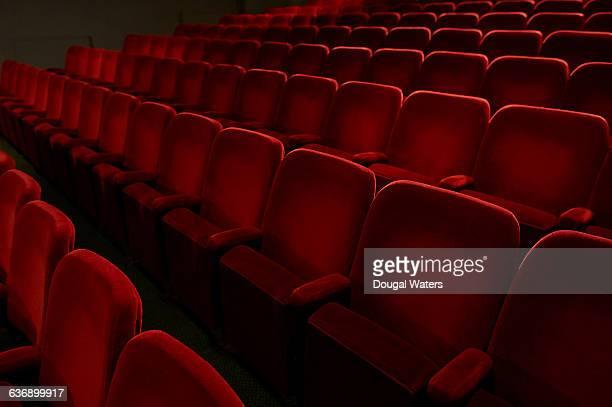 Red seats in empty theatre auditorium.