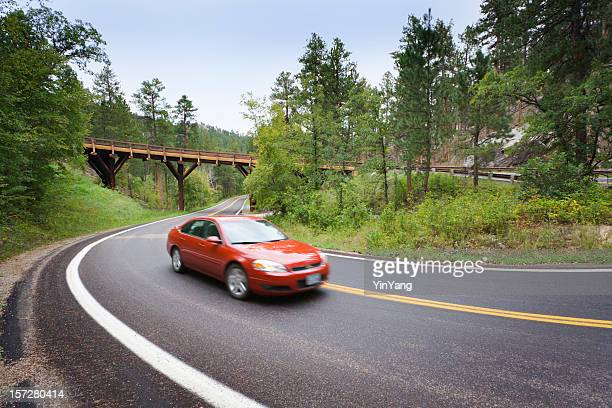 red sedan car driving scenic mountain highway with pigtail bridge - hairpin curve stock photos and pictures