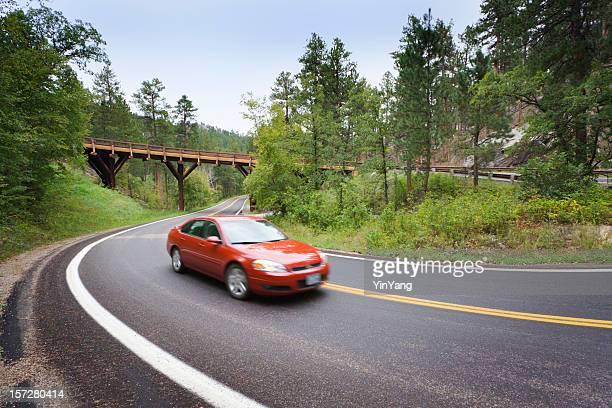 Rojo de sedán hacia el panorámico Mountain Highway puente con extremo libre (Pigtail