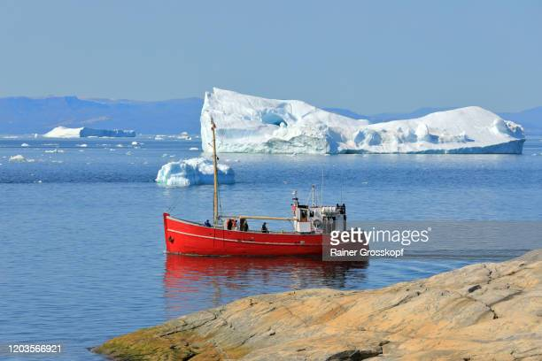 a red ship is passing some small bluish icebergs in arctic sea - rainer grosskopf stock pictures, royalty-free photos & images