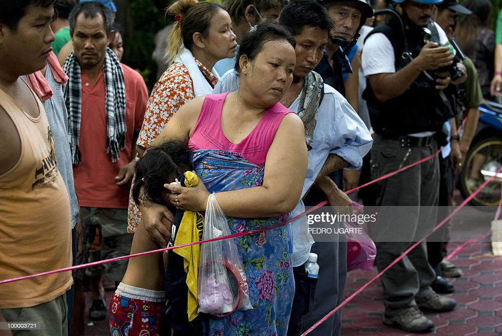 A Red Shirt anti-government protester covers her daugther as she looks at the bodies of protesters killed inside a temple which had been turned into a shelter within an anti-government protest site in downtown Bangkok on May 20, 2010. Thai police escorted thousands of protesters out of a Buddhist temple where they had cowered overnight after nine people were killed there in gunbattles.