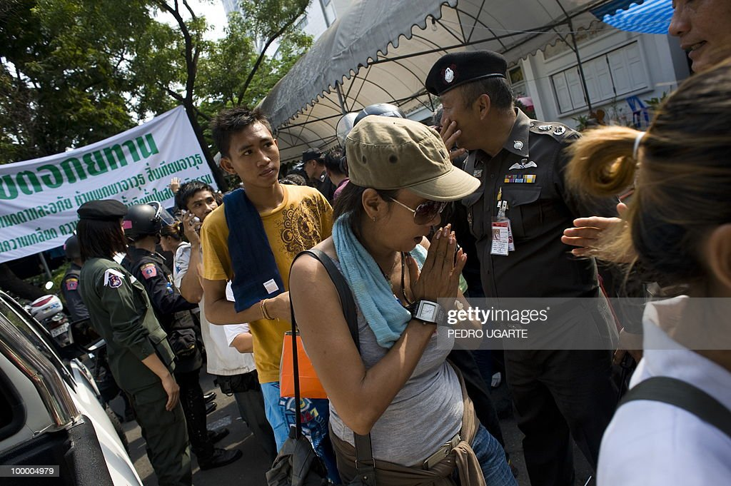 A ''Red Shirt'' anti-government protester greets at policemen as she leaves a temple which had been turned into a shelter within an anti-government protest site in downtown Bangkok on May 20, 2010. Gunshots rang out near a Buddhist temple in the heart of an anti-government protest zone in Bangkok, and soldiers were advancing on foot along an elevated train track, an AFP photographer saw. Thai security forces stormed the 'Red Shirts' protest camp on May 19 in a bloody assault that forced the surrender of the movement's leaders who asked their supporters to disperse.