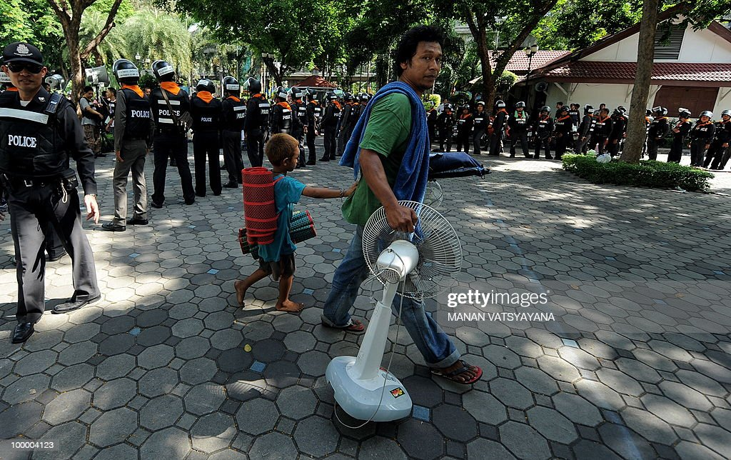 A 'Red Shirt' anti-government protester holds a fan as he arrives with his son at the Police headquarters in downtown Bangkok on May 20, 2010, after bieng moved from a temple which had been turned into a shelter within the protest site. Thai police escorted thousands of protesters out of a Buddhist temple where they had cowered overnight after nine people were killed there in gunbattles.