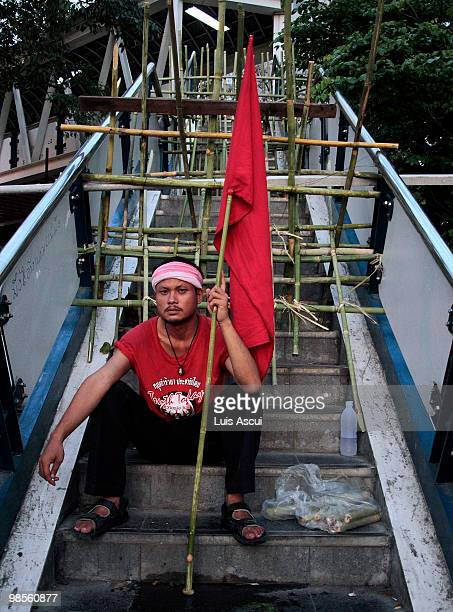 Red Shirt antigovernment protester holds a red flag while keeping a lookout for Thai army soldiers in the Silom district as the Red Shirt supporters...