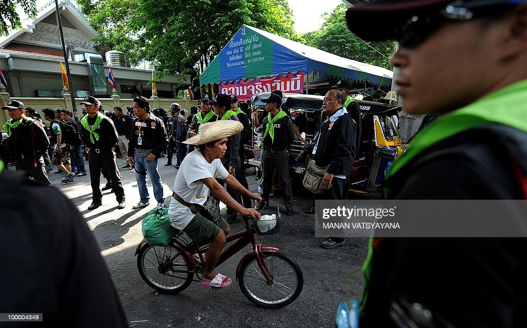 A Red Shirt anti-government protester rides his bicycle at the Police headquarters in downtown Bangkok on May 20, 2010 after bieng moved from a temple which had been turned into a shelter within the protest site. Thai police escorted thousands of protesters out of a Buddhist temple where they had cowered overnight after nine people were killed there in gunbattles.
