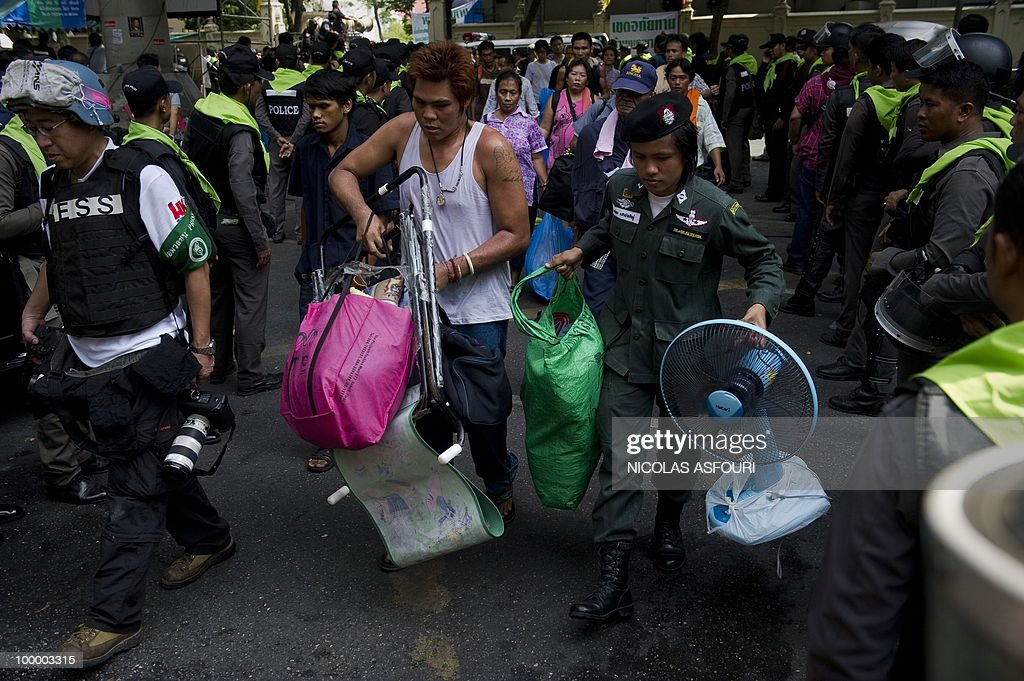 ''Red Shirt'' anti-government protesters leave a temple which had been turned into a shelter within an anti-government protest site in downtown Bangkok on May 20, 2010. Gunshots rang out near a Buddhist temple in the heart of an anti-government protest zone in Bangkok, and soldiers were advancing on foot along an elevated train track, an AFP photographer saw. Thai security forces stormed the 'Red Shirts' protest camp on May 19 in a bloody assault that forced the surrender of the movement's leaders who asked their supporters to disperse. AFP PHOTO/ Nicolas ASFOURI