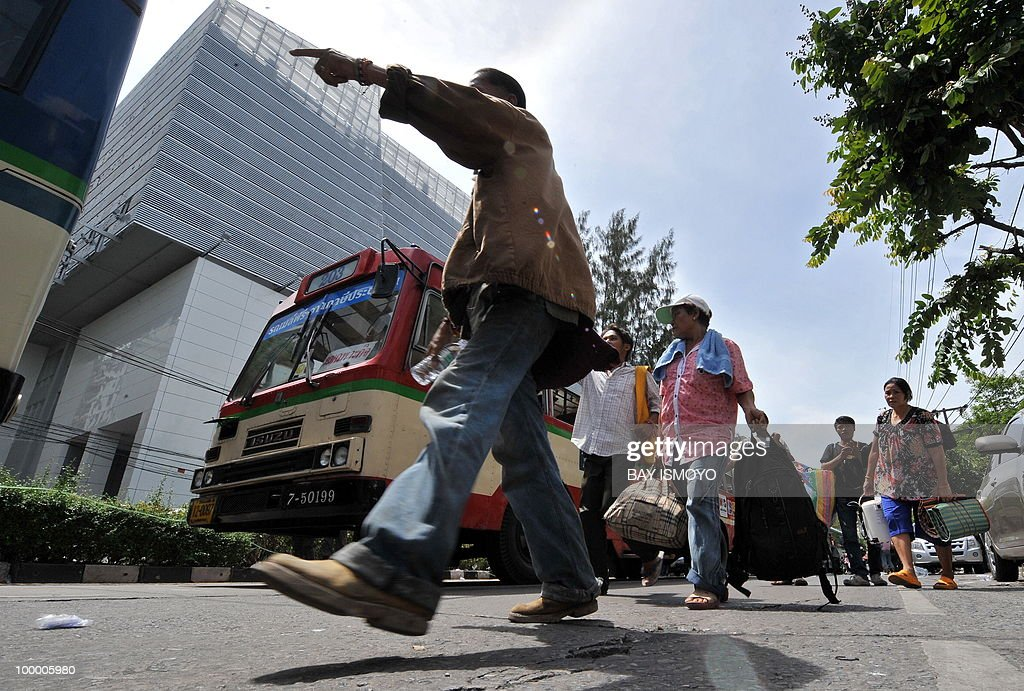 'Red Shirt' anti-government protestors carry their luggage before boarding buses out of their dismantled protest site a day after an army assault, in downtown Bangkok on May 20, 2010. Plumes of smoke hung over the Thai capital and gunfire crackled As troops moved to crush militants who went on the rampage after a deadly crackdown on their anti-government protest camp.