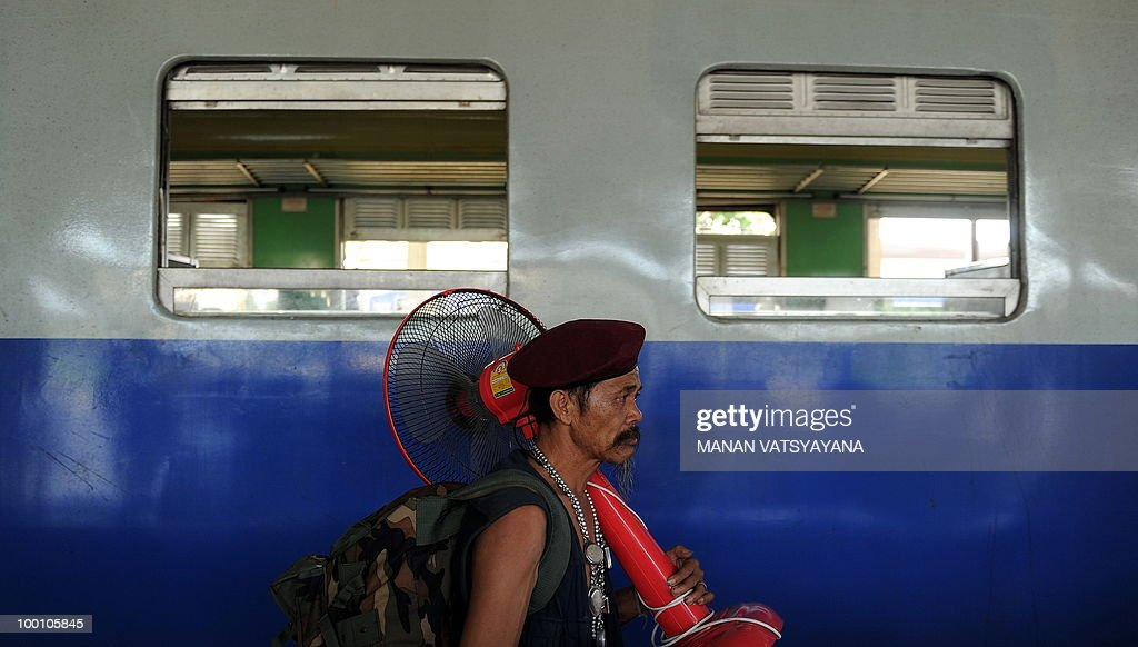 A Red Shirt protestor arriving on a train from Bangkok, carries a fan at the train station in Chiang Mai around 700kms from Bangkok on May 21, 2010. Thailand picked up the pieces after violence and mayhem triggered by a crackdown on anti-government protests, as the focus swung to recovery and reconciliation in a divided nation.