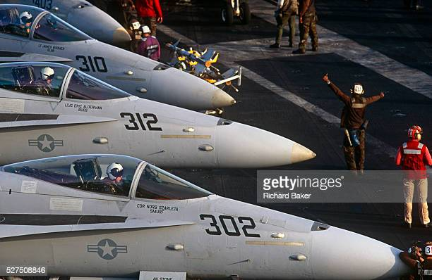 Red shirted ordnance men organise the busy deck of F/A-18C fighter jets on aircraft carrier on deck of USS Harry S Truman. Launched on 7 September...