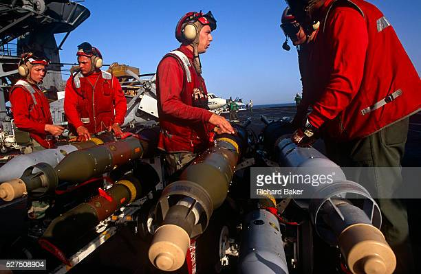 Red shirted ordnance men prepare to fit smart bombs and missiles to an F/A-18 fighter jet on deck of USS Harry S Truman. Launched on 7 September 1996...