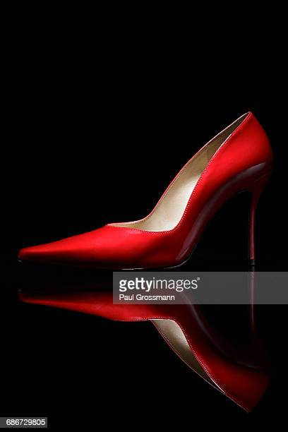 Red shoe against black background