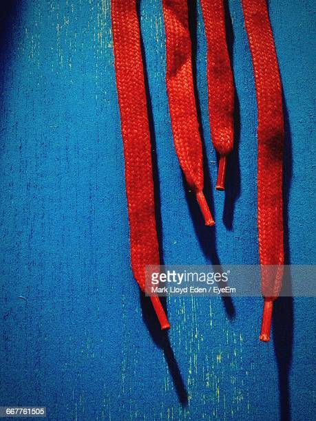 red shoelaces hanging against wall - shoelace stock pictures, royalty-free photos & images