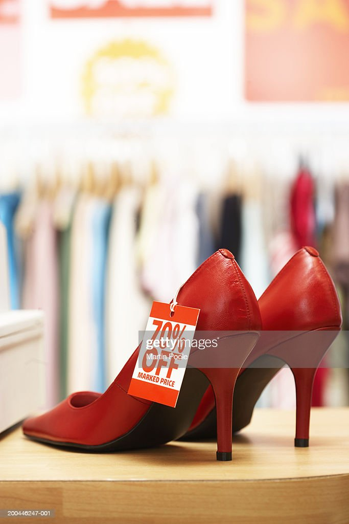 Red shoes on shop counter with discount tag attached, close-up : Stock Photo