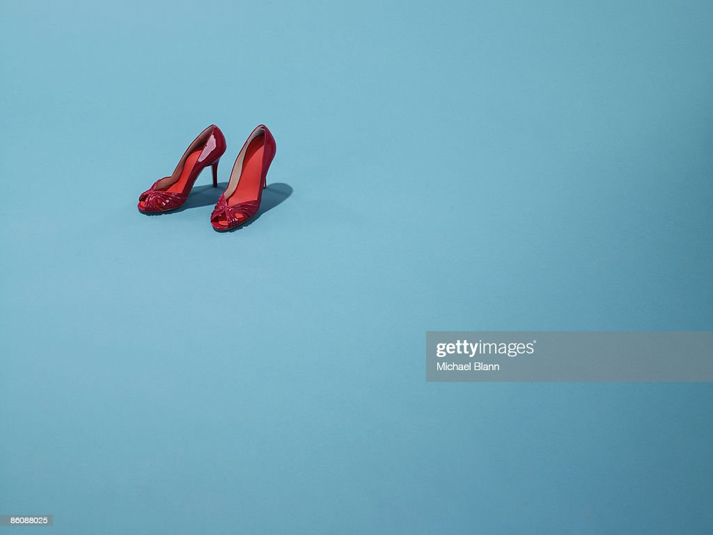 Red shoes sit on a blue backdrop : Stock Photo
