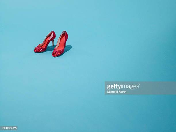 Red shoes sit on a blue backdrop