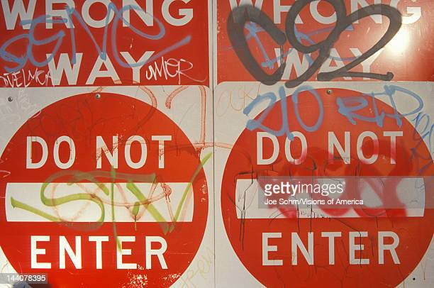 """Red signs reading """"Wrong Way, Do Not Enter"""" covered with graffiti Los Angeles"""
