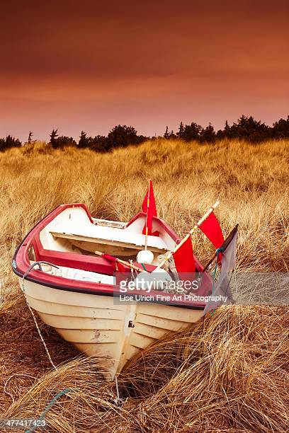 red skies and boat - lise ulrich stock pictures, royalty-free photos & images
