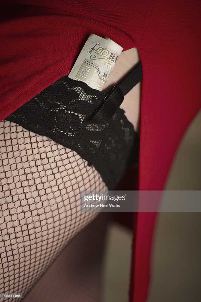 red skirt, stocking tops & a roll of pound notes : Stock Photo