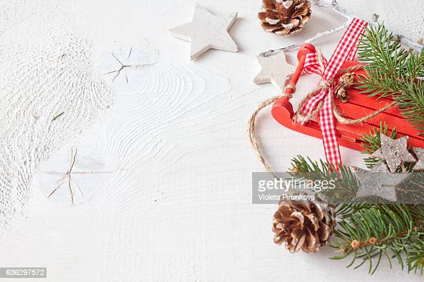 Red sleigh with Christmas decoration on white wood