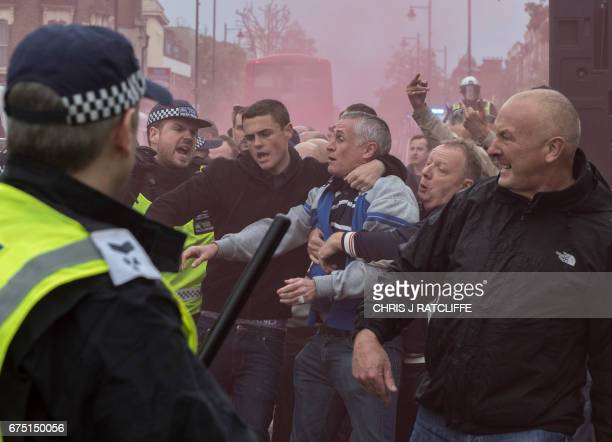 Red smoke fills the air during clashes between football fans as Arsenal supporters are escorted by police past Tottenham fans on their way into White...