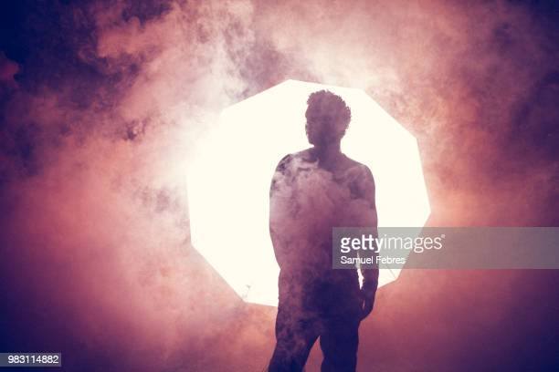 red smokey silhouette of a man at night - dry ice stock pictures, royalty-free photos & images