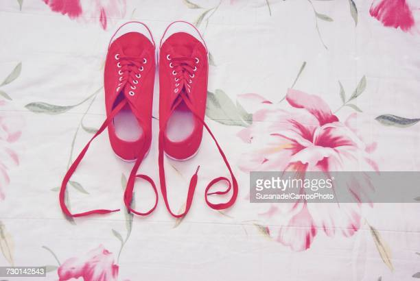 Red sneakers with shoelaces spelling the word love