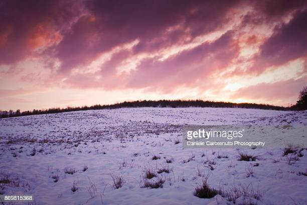 red snow sky at sunset - daniele carotenuto stock pictures, royalty-free photos & images