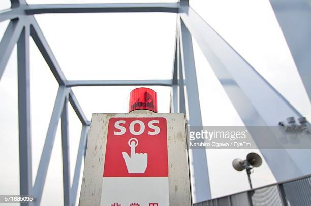 Red Sos Sign On Bridge Against Clear Sky