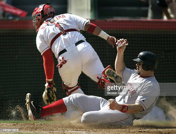 Red Sox catcher Jason Varitek slides in safely as the ball sails away from Anaheim catcher Benjie Molina on a fourth inning throwing error by Angels...