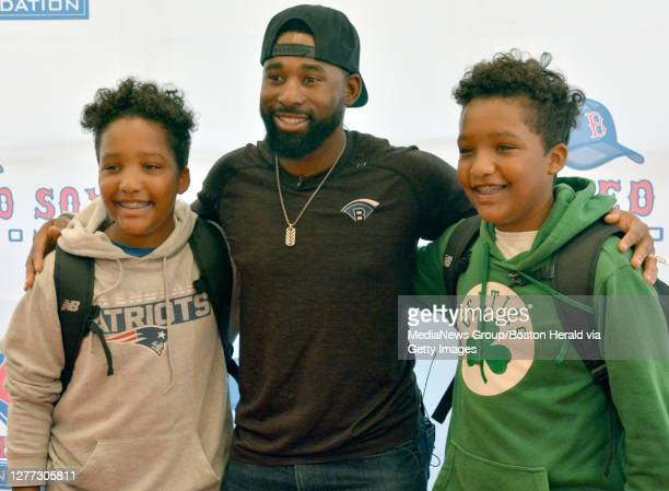 Red Sox center fielder Jackie Bradley Jr. Poses with Red Sox Scholars and twins Jaleel and Ayden Cardosa after they received backpacks filled with...