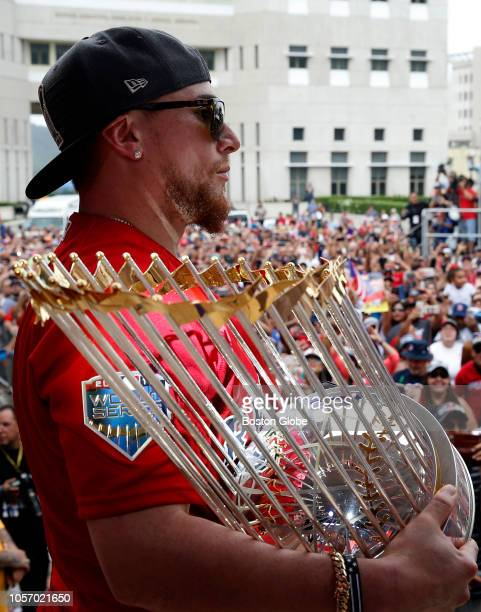 Red Sox Christian Vasquez holds the World Series trophy on stage at a rally in Caguas Red Sox manager Alex Cora and some players took the World...