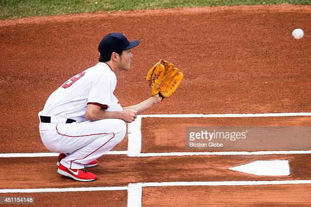 Red Sox closer Koji Uehara finds himself in an unusual position catching a ceremonial pitch from the Japanese Consul General in Boston Akira Muto...