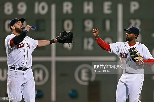 Red Sox left fielder Jonny Gomes left is already snacking as he high fives center fielder Jackie Bradley Jr right following Boston's 40 victory their...