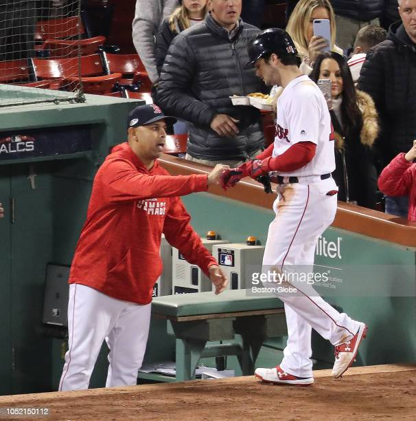 Red Sox manager Alex Cora congratulates Andrew Benintendi after scoring in the first inning Boston Red Sox hosted the Houston Astros in Game Two of...