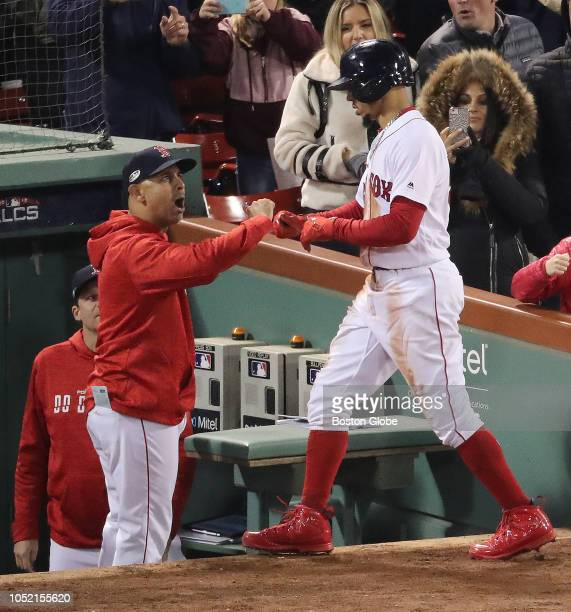 Red Sox manager Alex Cora greets Mookie Betts after he scored in the seventh inning Boston Red Sox hosted the Houston Astros in Game Two of ALCS at...