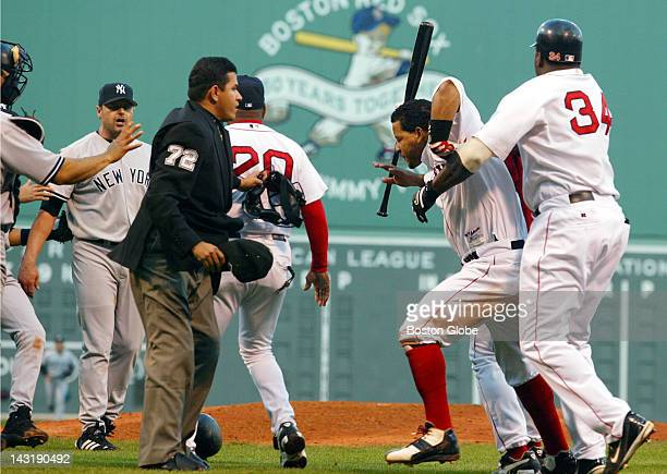 Red Sox' Manny Ramirez is held back by teammate David Ortiz as he tries to get to Yankees pitcher Roger Clemens during fourth inning fight