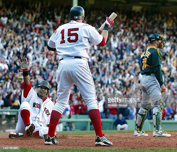 Red Sox Manny Ramirez left signals 'safe' as he slides across the plate with what would be the game winning run scoring on teammate David Ortiz'...