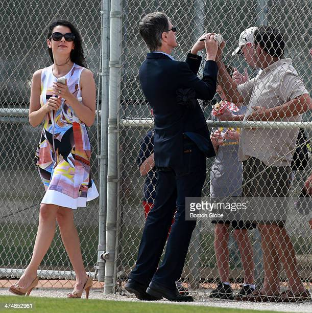 Red Sox owner John Henry right signs an autograph for a fan with his wife Linda Pizzuti left during Boston Red Sox spring training at JetBlue Park on...