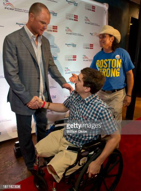 Red Sox pitcher Jon Lester shakes hands with Boston Marathon bombing victim Jeff Bauman and Carlos Arredondo before participating in a Hollywood...