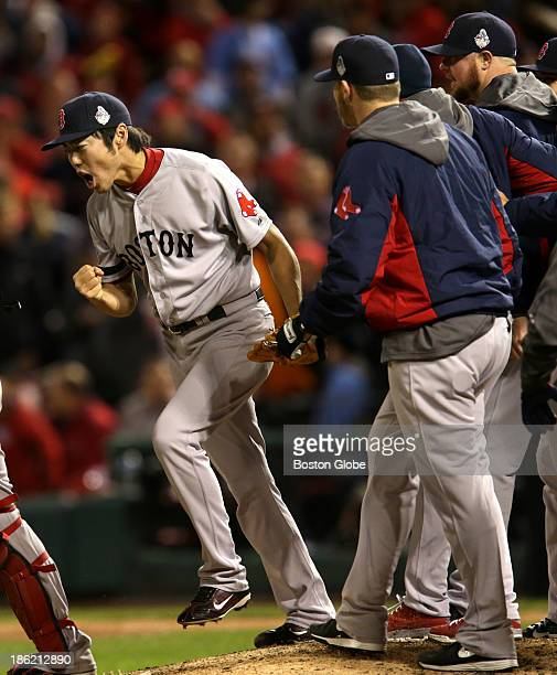Red Sox pitcher Koji Uehara is joined by teammates to celebrate after he picked Kolten Wong of the Cardinals off first base to end the game The St...