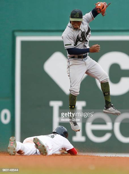 Red Sox player Andrew Benintendi dives into second safely before Braves Ronald Acuna Jr could make the catch during the sixth inning of a game...